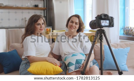 Two beautiful plus size girlfriends shooting video for internet blog sitting at home. Oversize girls vloggers recording video about healthy dieting and overweight using professional camera