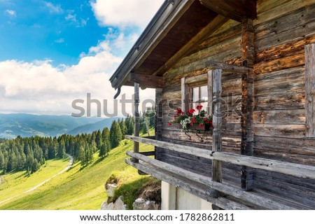 Idyllic alpine wooden mountain hut scenery in Austrian alps, forest trees and  green meadows, sunny day, blue sky Royalty-Free Stock Photo #1782862811