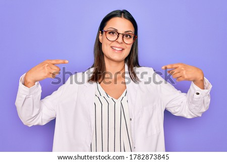Young beautiful brunette psychologist woman wearing coat and glasses over purple background looking confident with smile on face, pointing oneself with fingers proud and happy.