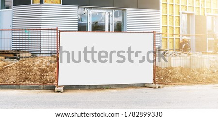 large white banner with place for template between metal fence against building with windows reflecting summer morning sunlight