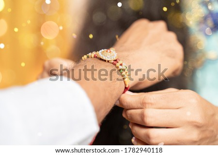 Closeup of hands, sister tying rakhi, Raksha bandhan to brother's wrist during festival or ceremony - Rakshabandhan celebrated across India as selfless love or relationship between brother and sister