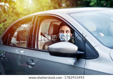 Beautiful Indian young woman in a mask sitting in a car, protective mask against coronavirus, driver on a city street during covid-19 pandemic Royalty-Free Stock Photo #1782955493