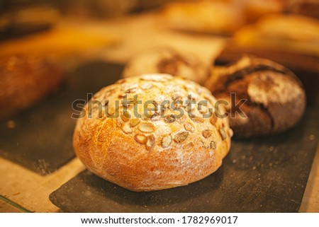 Village bread. Round bread. Bread showcase. Bakery. Homemade baked bakery rooty, fresh round bread with pumpkin seeds, with organic wheat flour. Fresh and organic soft tack oven glass case #1782969017