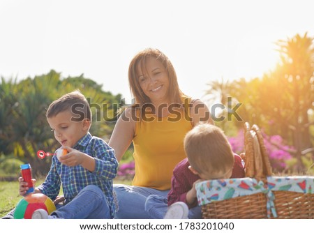 Happy mother enjoy day with her twin sons in a nature park - Family and pic nic - Mother and child love - Focus on the mothers face