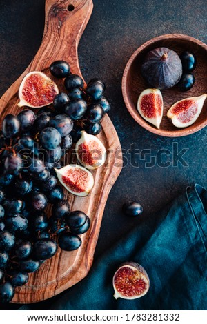 Autumn food still life with blue grape and ripe figs.