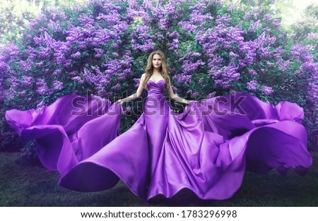 Fashion Model in Lilac Flowers, Young Woman in Beautiful Long Dress Waving on Wind, Outdoor Beauty Portrait in Blooming Garden Royalty-Free Stock Photo #1783296998