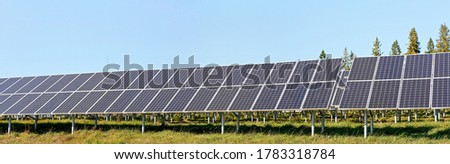 Solar photovoltaic panels on green grass meadow, clear sky above trees background, wide banner photo