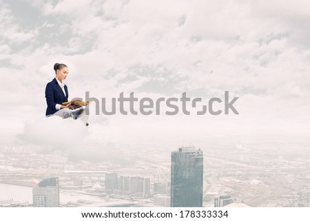Young attractive businesswoman sitting on cloud and reading book #178333334