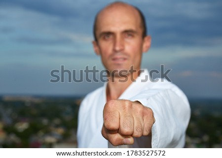 In karategi, an adult athlete trains a punch against the sky Royalty-Free Stock Photo #1783527572