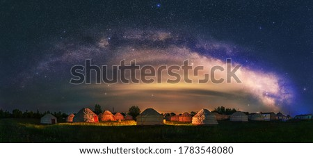 Under the bright Milky Way, Mongolia yurts on the grassland are scattered.  Royalty-Free Stock Photo #1783548080