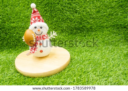 Snowman with American Football on green grass background for Soccer #1783589978