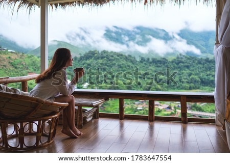 Portrait image of a beautiful asian woman holding and drinking hot coffee , sitting on balcony and looking at mountains and green nature