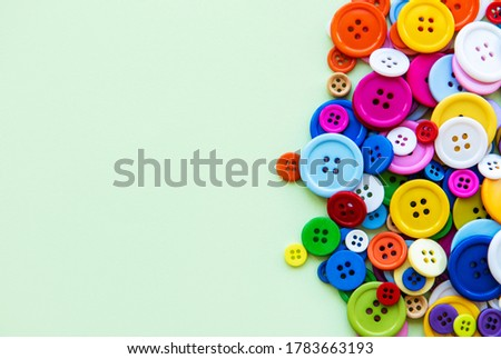 Colored sewing buttons composition on green pastel background. Flat lay with copy space. Royalty-Free Stock Photo #1783663193
