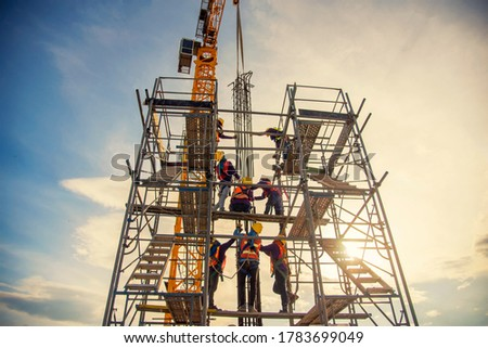 group of worker in safety uniform install reinforced steel column in construction site during sunset time #1783699049