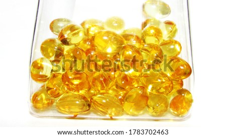 Cod liver oil  or fish oil gel capsule  contqin in jar on white background. It contains omega 3 fatty acids , EPA,  DHA