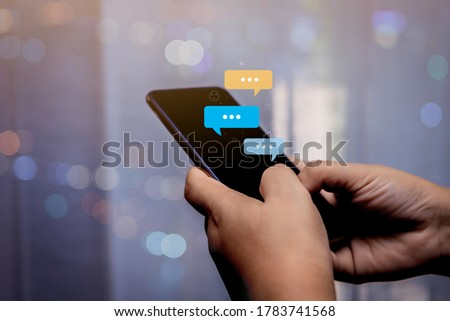 Person hand using smartphone typing, chatting conversation in chat bubble pop-up. Social media maketing concept. Royalty-Free Stock Photo #1783741568