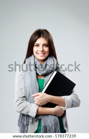 Young cheerful woman standing and holding a book on gray background Royalty-Free Stock Photo #178377239