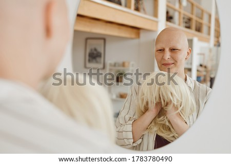 Reflection portrait of bald adult woman looking in mirror holding wig while standing in warm-toned home interior, alopecia and cancer awareness, copy space Royalty-Free Stock Photo #1783780490