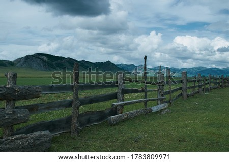wooden fence in a valley among the mounta               #1783809971