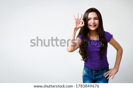 Portrait image of very happy amazed smiling brunette little cute girl, in violet smart casual clothing, showing ok or zero hand sign gesture, isolated against grey color background with copy space.