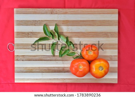 This is a picture of some Tomatoes and curry leaves.