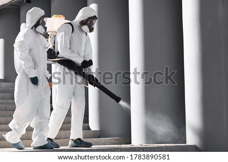 professional cleaning and disinfection at town complex amid the coronavirus epidemic. two workers prevent and control epidemic. in protective suit and mask #1783890581