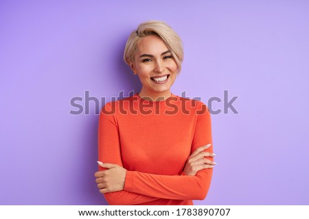 portrait of positive charming short-haired lady of caucasian appearance isolated over purple background. young emotional female looks at camera and smile