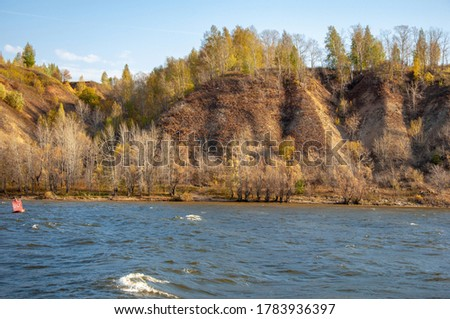Autumn landscape, dark blue water, last warm days, river, trees, windy weather, yellow-red autumn leaves #1783936397