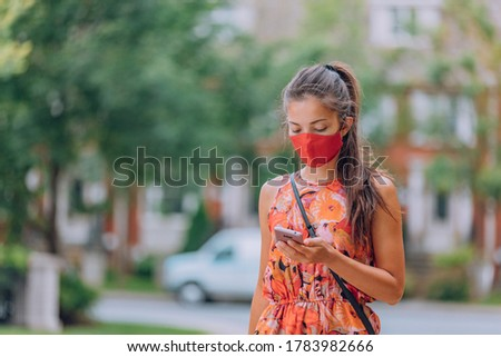 COVID-19 mask wear mandatory in city. Asian woman walking using mobile phone wearing face mask protection as prevention for coronavirus outside in city park summer lifestyle outdoor. Corona virus. #1783982666