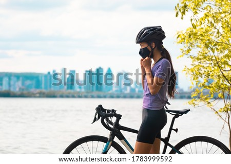 Wearing covid-19 mask while riding bike. Sport cyclist woman biking putting on face mask for Covid-19 prevention during summer outdoor leisure exercise activity. Fitness outside. #1783999592