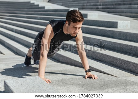 Active leisure and motivation. Millennial guy in sportswear with fitness tracker push up the city stairs at sunlight, free space Royalty-Free Stock Photo #1784027039