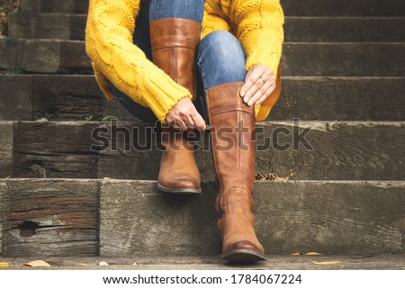Woman sitting on stairs and fasten zipper on her leather boots. Autumn fashion concept Royalty-Free Stock Photo #1784067224