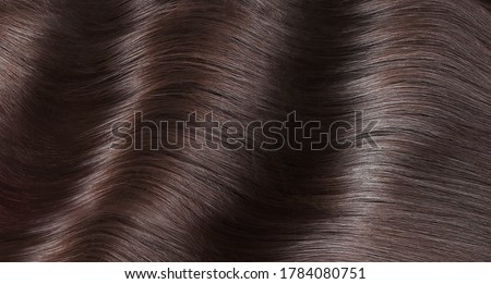 A closeup view of a bunch of shiny straight brown hair in a wavy curved style. Royalty-Free Stock Photo #1784080751
