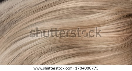 A closeup view of a bunch of shiny straight blond hair in a wavy curved style.