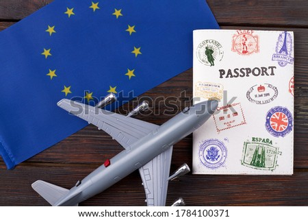 Flight to europe concept. European union flag with passport and toy airplane on dar wooden background.