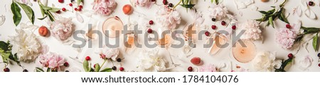 Rose wine variety layout. Flat-lay of rose wine in glasses with flowers and summer fruit over white background, top view, wide composition. Summer drink for party, wine shop or wine tasting concept #1784104076
