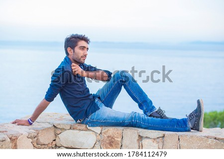 Man thinking looking to blue sky while sitting on a concrete bridge above the sea taking deep breath enjoying freedom at sunset sea on background. Melancholic thoughtful person, peace mind concept. #1784112479