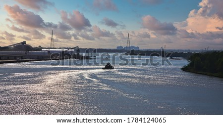 A tugboat heading down the Savannah River in the late afternoon lightg #1784124065