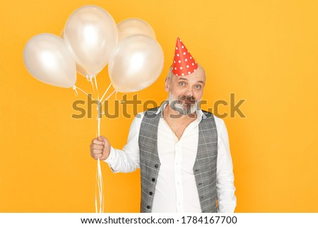 Mature man with gray beard celebrating anniversary. Isolated image of handsome unshaven male pensioner holding helium balloons having fun at birthday party. Holiday, celebration and ahing concept