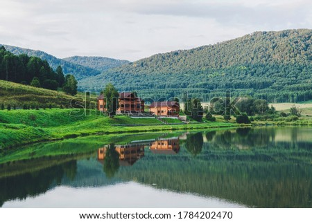 Beautiful landscape of mountains and lakes. The log house is reflected in the clear water. Tourist base in the mountains. Country house for environmentally friendly outdoor recreation #1784202470