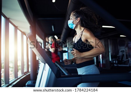 Active fitness woman wearing hygienic protective face mask while training in gym to protect herself and others against coronavirus or covid-19. Stay safe and healthy. #1784224184