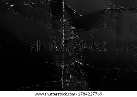 Abstract worn black background from crumpled paper. Old damaged surface with wrinkles and dust. Folded cardboard Royalty-Free Stock Photo #1784227769