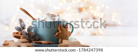 Hot winter drink: chocolate with whipped cream in blue mug. Christmas time. Cozy home atmosphere, white background. Homemade gingerbread cookies, christmas lights. Banner, copy space for text #1784247398