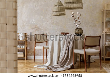Stylish and elegant dining room interior with diner table, design chairs, rattan pendant lamps, dried flowers in vases, furniture, decoration and elegant personal accessories in cozy home decor. Royalty-Free Stock Photo #1784248958