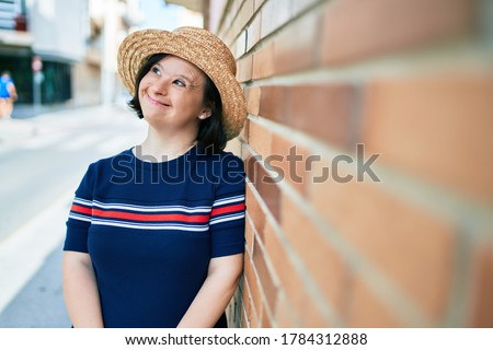 Beautiful brunette woman with down syndrome wearing a summer hat at the town on a sunny day leaning on a bricks wall Royalty-Free Stock Photo #1784312888