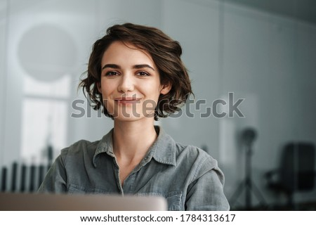 Image of young beautiful joyful woman smiling while working with laptop in office #1784313617
