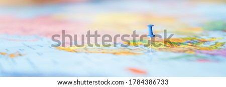 Pushpin showing the location of a destination point on a map. Travel destination, pin on the map. Very selective focus, blur on all edges and special lightening. Blue pushpin Royalty-Free Stock Photo #1784386733