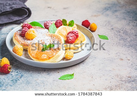 Japanese fluffy pancakes with raspberries in a gray plate, gray background. Japanese cuisine concept. Royalty-Free Stock Photo #1784387843