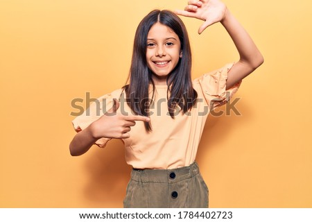 Beautiful child girl wearing casual clothes smiling making frame with hands and fingers with happy face. creativity and photography concept.