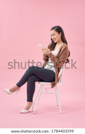 Portrait of a satisfied casual asian woman using mobile phone while sitting on a chair over pink background Royalty-Free Stock Photo #1784403599